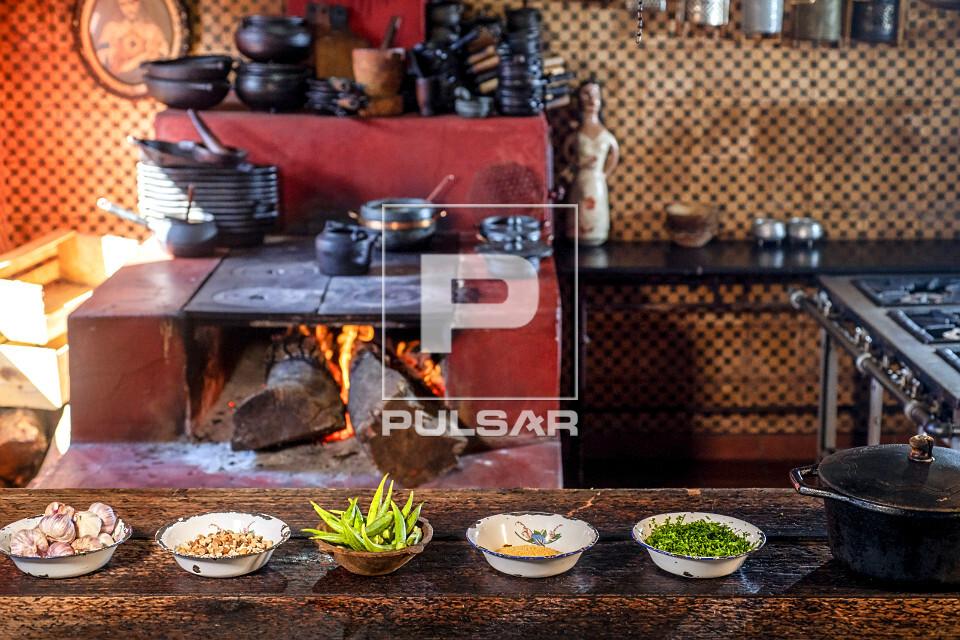 Ingredientes da cozinha mineira e fogão à lenha ao fundo