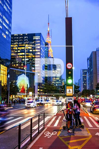 Semáforo para ciclistas, ciclovia e edifícios comerciais na Avenida Paulista ao anoitecer - Torre Cásper L�