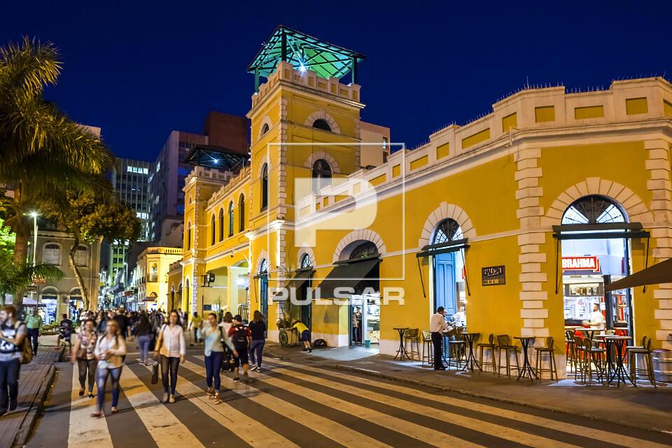 Vista noturna de pessoas na faixa de pedestres em frente ao Mercado Público Municipal