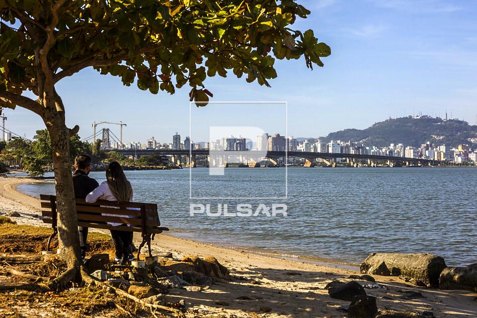 Casal sentado em banco embaixo de árvore observando a Ponte Colombo Salles e Ponte Pedro Ivo Campos - liga a