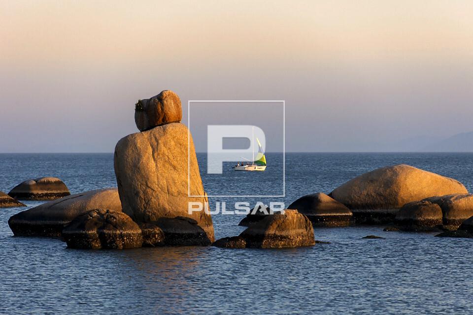 Formações rochosas na Praia de Itaguaçu ao entardecer - ao fundo barco a vela