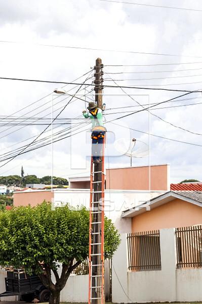 Trabalhador fazendo manutenção em rede de fibra ótica - internet em bairro residencial