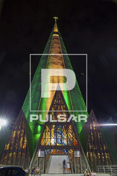 Vista noturna da Catedral Nossa Senhora da Glória iluminada com as cores verde e amarela - projeto do arquite