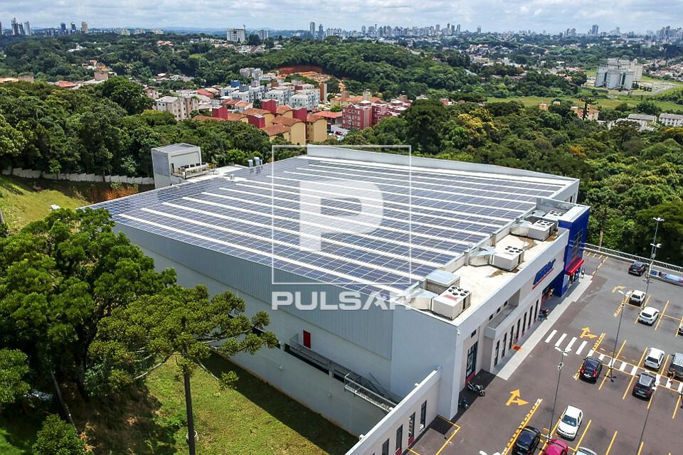 Vista de drone das placas fotovoltaicas de energia solar no telhado de supermercado