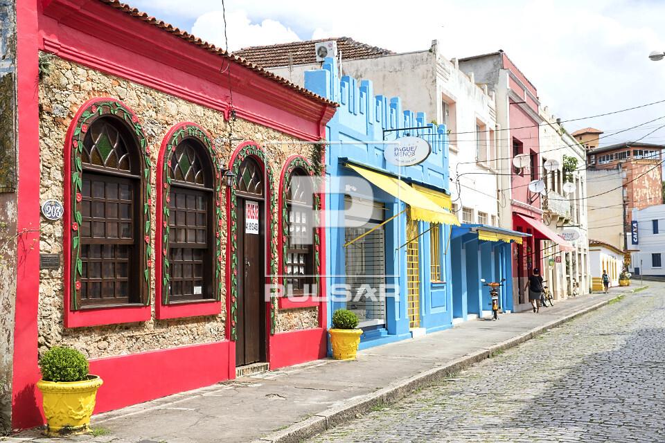 Prédios comerciais com fachada na calçada - destaque para a parede construída com pedregulhos e conchas mar