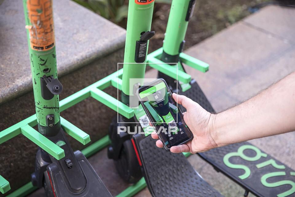 Mão de pessoa habilitando uso de patinete compartilhada - locação por meio de aplicativo no celular via blu