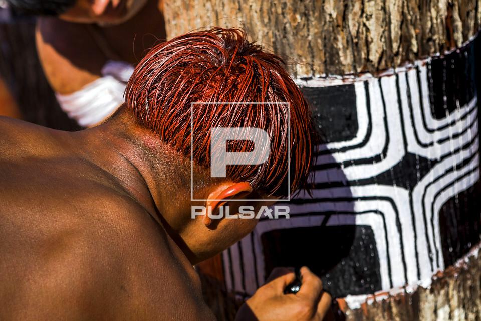 Indígena da aldeia Afukuri etnia Kuikuro pintam troncos de madeira que simbolizam os mortos homenageados dura