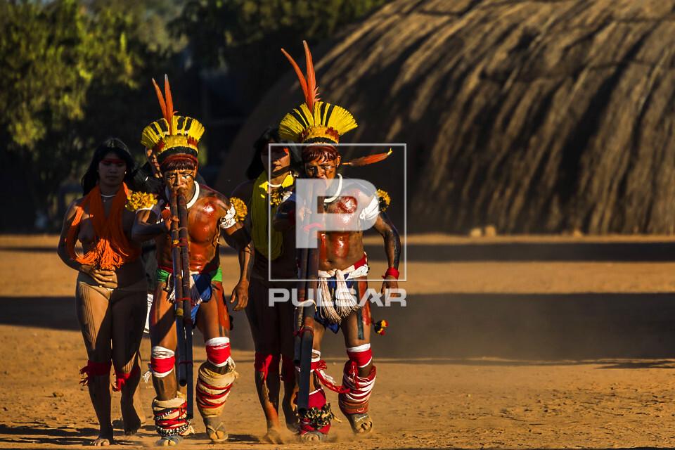 Indígenas da aldeia Afukuri etnia Kuikuro tocando flauta uruá com duas jovens ao fundo na cerimônia do Kuar