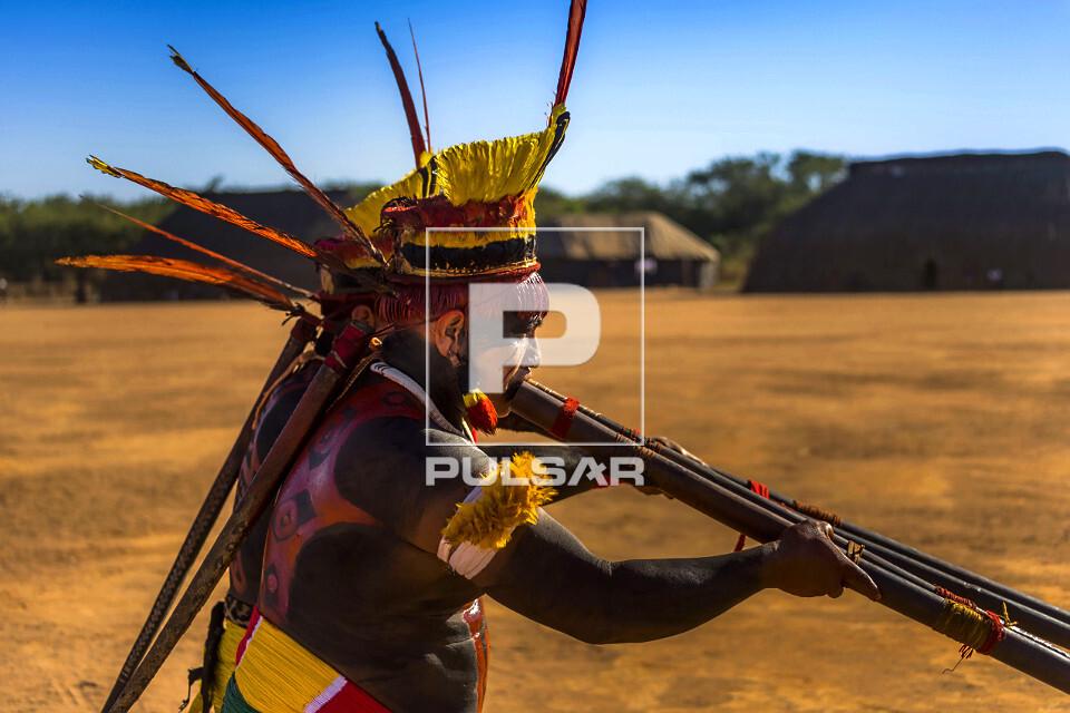 Indígena da aldeia Afukuri etnia Kuikuro tocando flauta uruá na cerimônia do Kuarup no Parque Indígena do