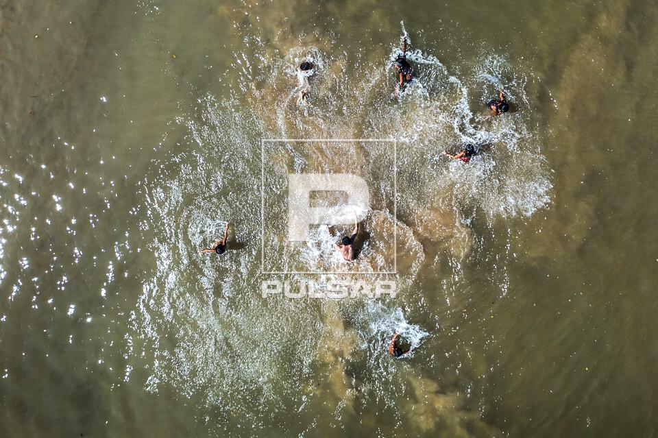 Vista de drone de crianças indígenas da Aldeia Afukuri e etnia Kuikuro brincando nos bancos de areia do rio