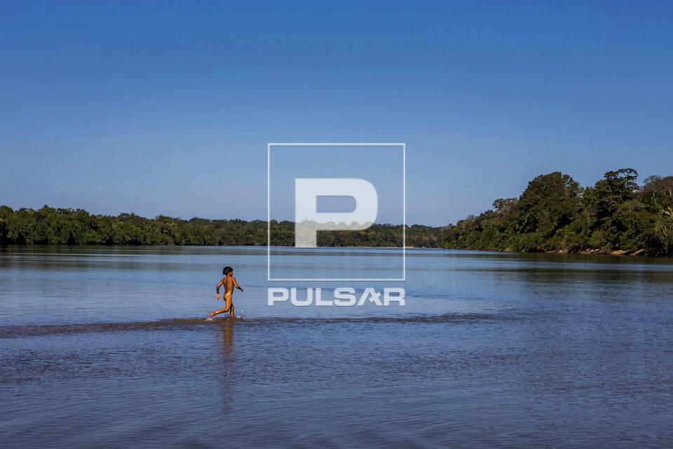 Criança indígena da Aldeia Afukuri e etnia Kuikuro correndo sobre banco de areia do rio Culuene - Parque Ind