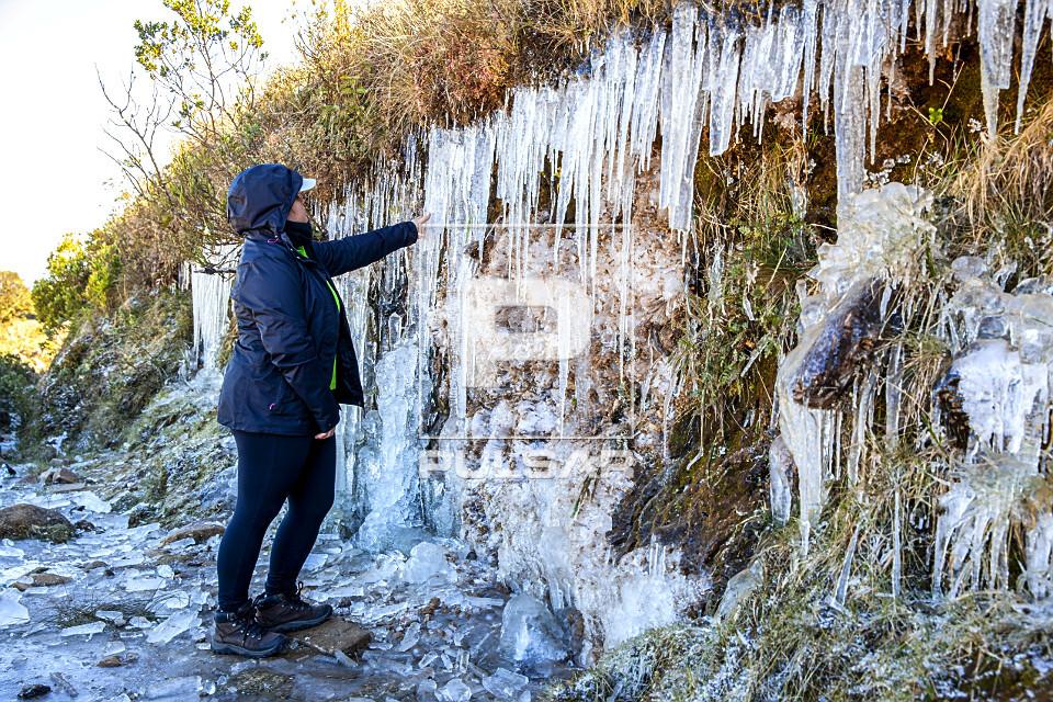 Turista contemplando gelo formado em barranco