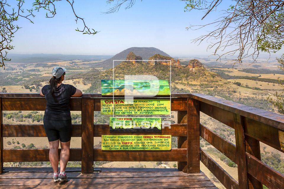 Ecoturista contemplando a paisagem a partir do deck de madeira no alto da Pedra do Índio - ao fundo Três Ped