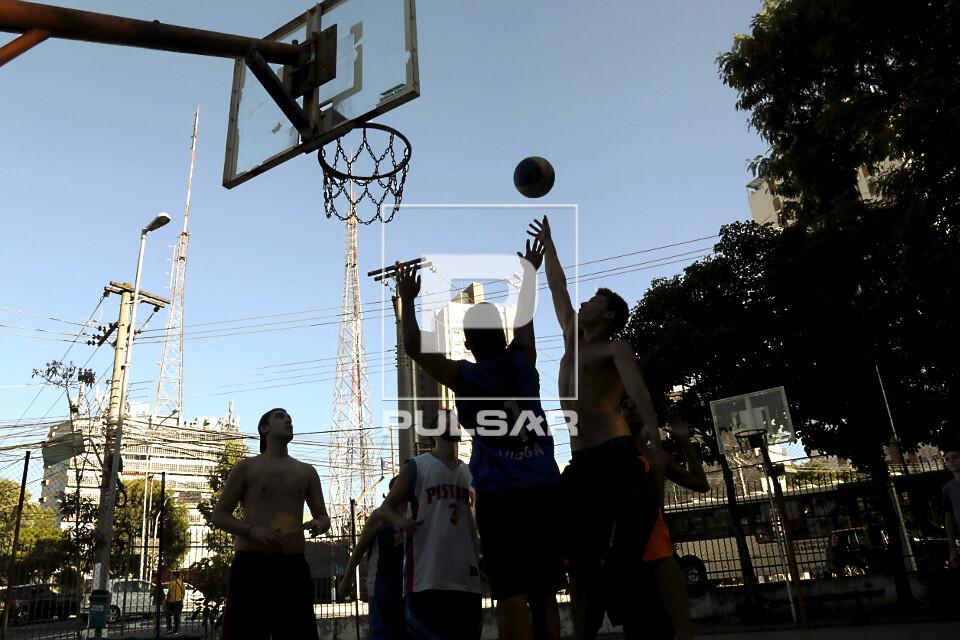 Pessoas jogando basquete em quadra de praça púbica