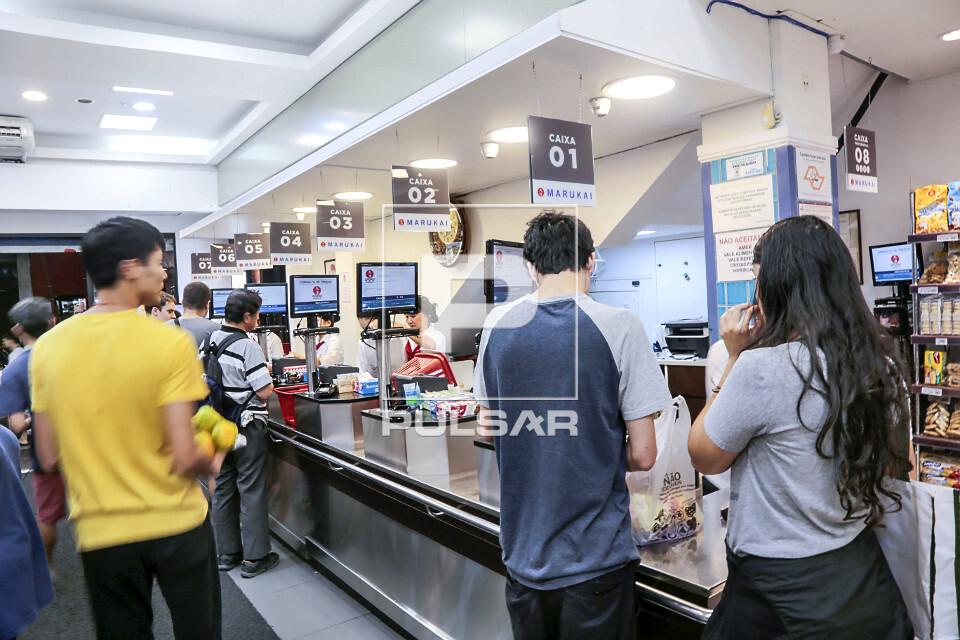 Caixas atendendo consumidores em mercado de produtos alimentícios industrializados de origem japonesa no Bair
