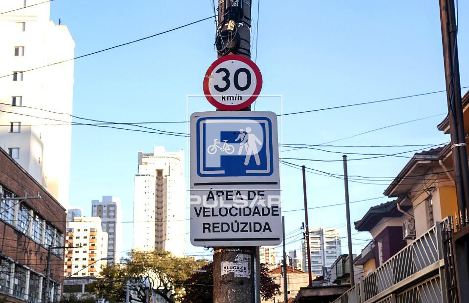 Placa indicando área de velocidade reduzida de 30 km/h devido grande circulação de pedestres e ciclistas na