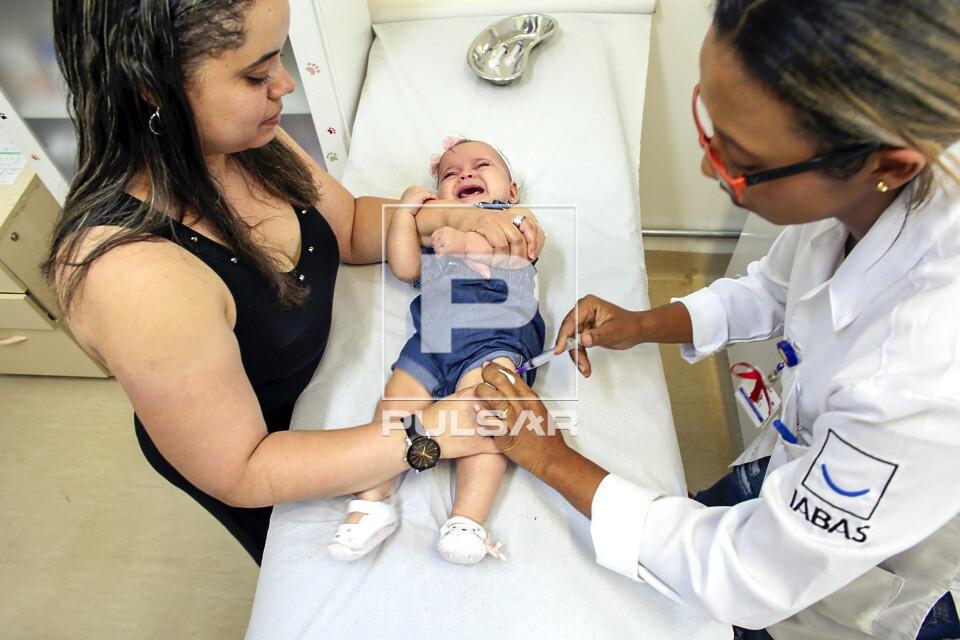 Técnica de enfermagem aplica várias vacinas em criança segurada pela mãe no Dia D na UBS Unidade Básica d