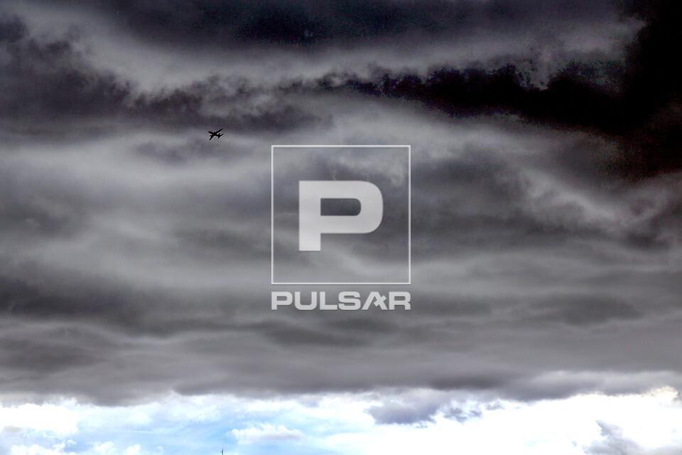 Nuvens de chuva sobre a cidade com detalhe de avião voando nas proximidades