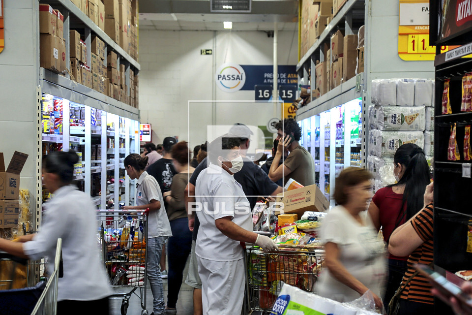 Pandemia Coronavírus - cliente com máscara e luvas na fila de caixa de grande supermercado - movimento inten