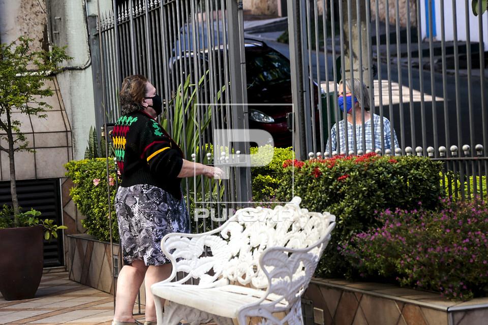 Senhoras conversam usando máscaras e mantendo distanciamento social durante pandemia do coronavírus - bairro