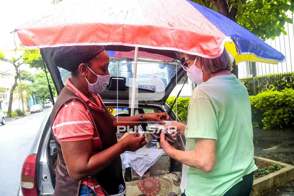 Vendedora ambulante de queijos entrega troco para cliente - bairro Perdizes - uso de máscaras de proteção d