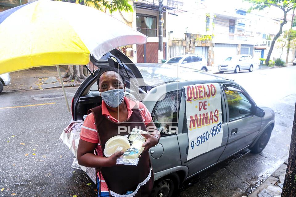 Vendedora ambulante de queijos exibe variedades do produto no bairro Perdizes - uso de máscara de proteção