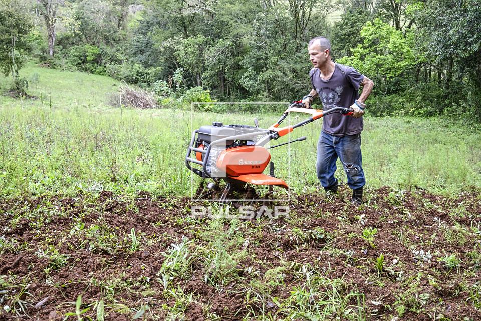 Agricultor arando a terra com motocultivador em pequena propriedade rural