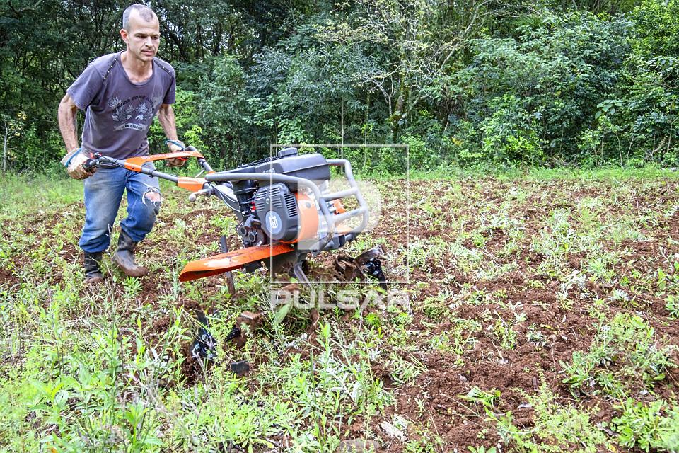 Agricultor arando a terra com motocultivador em propriedade rural