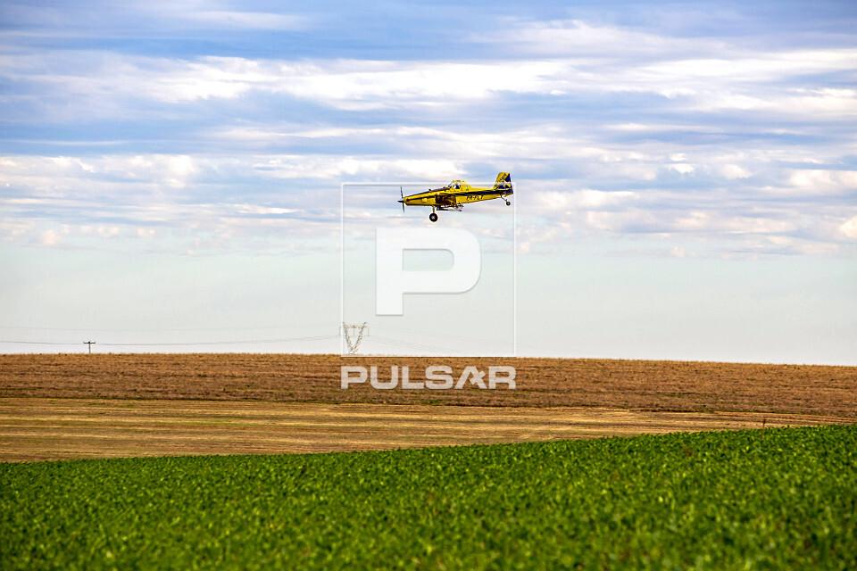 Avião agrícola aplicando uréia granulada sobre plantação de milho em propriedade rural