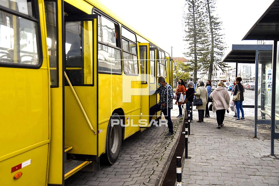 Pessoas embarcando em ônibus no centro histórico