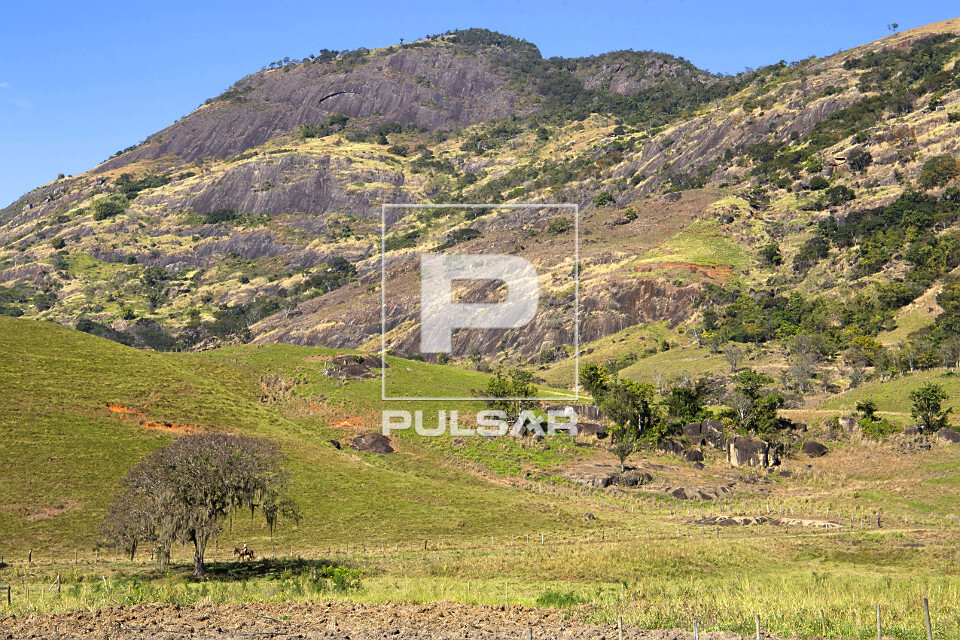 Paisagem rural com formações rochosas as fundo