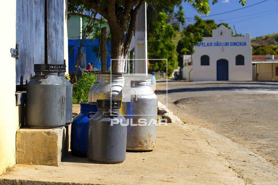 Galões de leite bovino de fazenda para coleta na beira de estrada rural