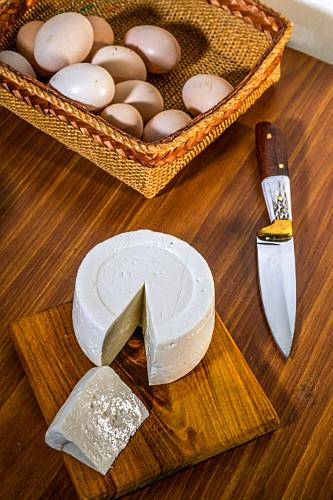 Queijo artesanal frescal da região do cerrado mineiro e ovos ao fundo