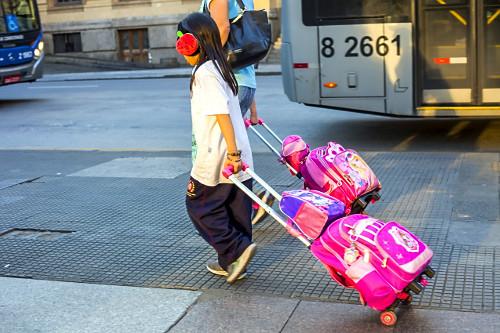 Criança com fone de ouvido carregando mochila e lancheira em carrinho de mão