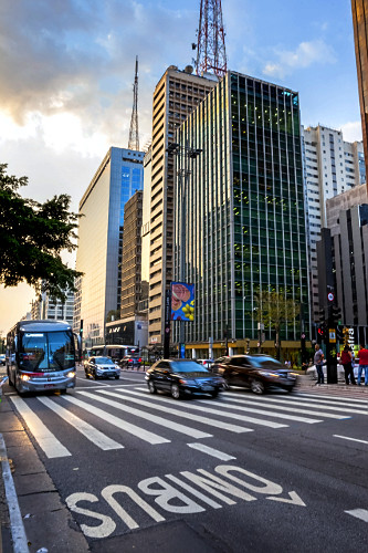 Edifícios comerciais e veículos trafegando na Avenida Paulista - destaque para faixa de pedestres e corredor