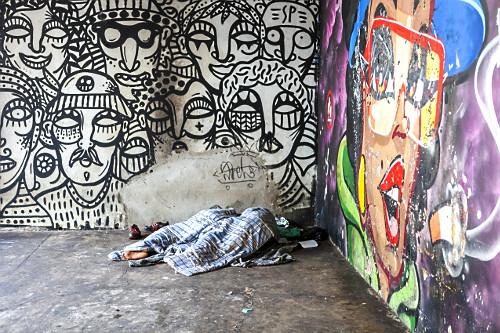 Grafite em parede e moradores de rua dormindo em calçada na Avenida Paulista - centro da cidade