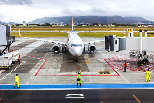 Aeronave no Aeroporto Internacional Hercílio Luz e sinalizador orientando manobra de estacionamento
