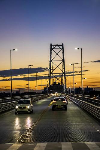 Veículos trafegando na Ponte Hercílio Luz ao entardecer - liga a ilha de Santa Catarina ao continente - inau