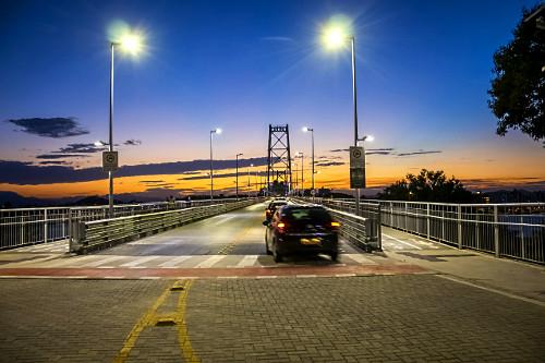 Veículo trafegando na Ponte Hercílio Luz iluminada ao anoitecer - liga a ilha de Santa Catarina ao continent
