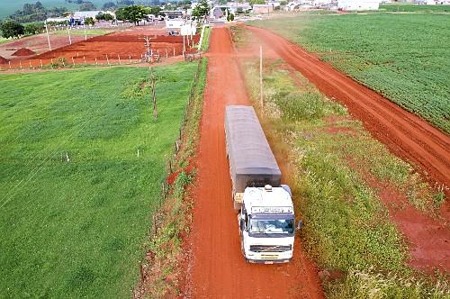 Vista de drone de caminhão carregado de soja trafegando em estrada rural com plantação de soja no entorno