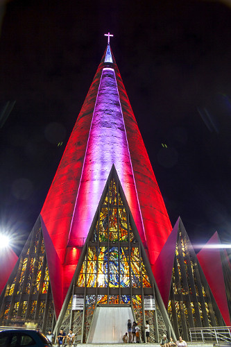 Vista noturna da Catedral Nossa Senhora da Glória iluminada com a cor rosa - projeto do arquiteto José Augus
