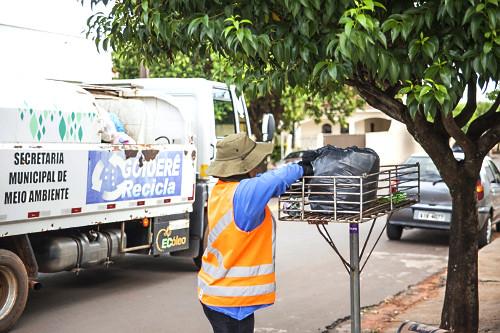 Coletor de lixo catando saco plástico de cesto durante coleta de lixo reciclável