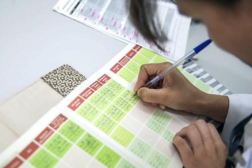Mãos de enfermeira preenchendo carteira de vacinação em posto pelo SUS - Sistema Único de Saúde