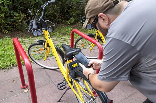 Pessoa habilitando uso de bicicletas compartilhada - locação por meio de aplicativo no celular via bluetooth