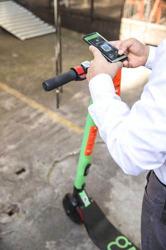 Mãos de pessoa habilitando uso de patinete compartilhada - locação por meio de aplicativo no celular via bl