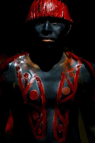 Jovem indígena da aldeia Afukuri - etnia Kuikuro - com cabelos pintados com urucum e corpo pintado com jenipa