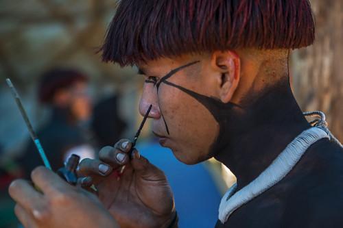 Jovem indígena da aldeia Afukuri e etnia Kuikuro pintando o rosto para cerimônia do Kuarup - Parque Indígen