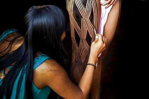 Jovem indígena da aldeia Afukuri e etnia Kuikuro pintando o corpo para a cerimônia do Kuarup no Parque Indí