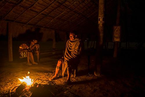 Ancião indígena da Aldeia Afukuri e etnia Kuikuro junto a fogueira - ao fundo jovens usando telefone celular