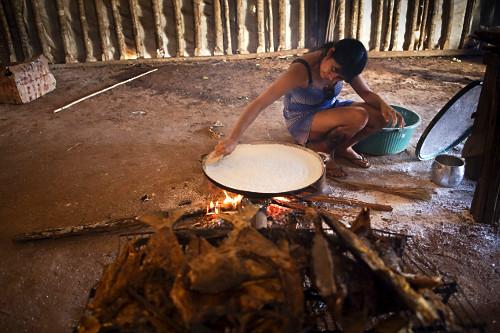 Jovem indígena da Aldeia Afukuri e etnia Kuikuro assando beiju na fogueira durante cerimônia do Kuarup - Par